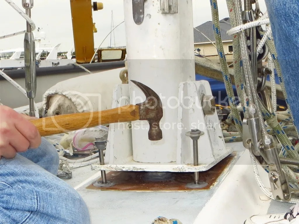 Hammering bolts to step the mast
