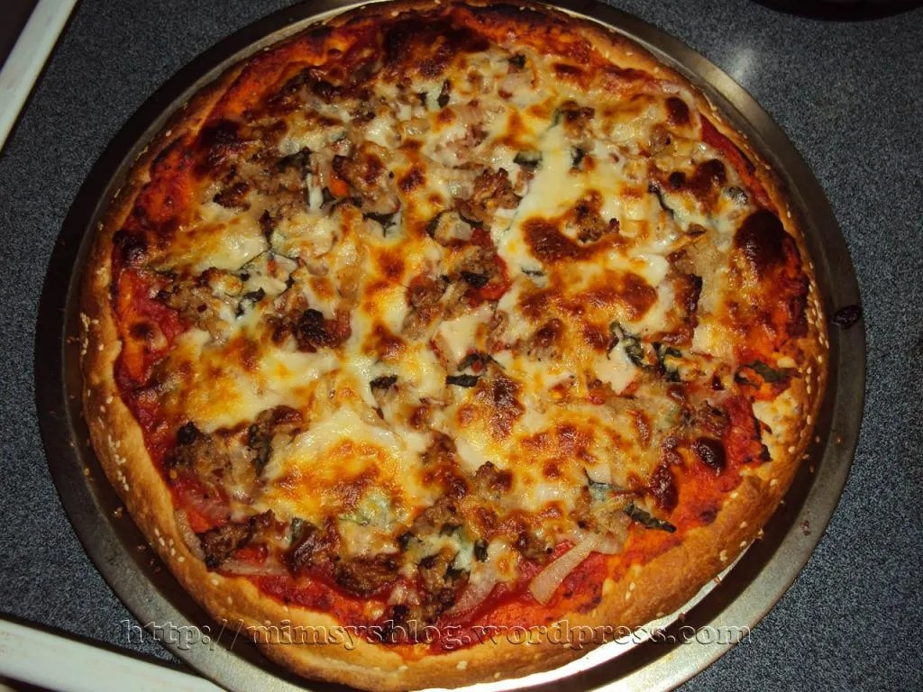 Homemade Pizza with Italian Sausage, Sauteed Onions, Fresh Basil and Cheese.