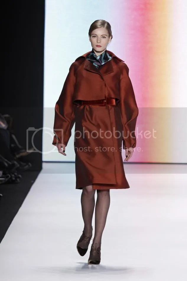 28. Ieva: Rust silk and wool organdy trench, turquoise feather print silk crêpe blouse and skirt, rust velvet belt.
