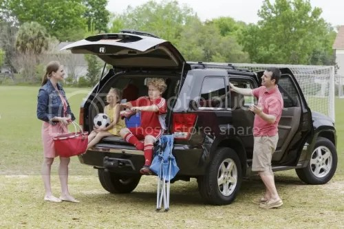 family in a minivan at a park