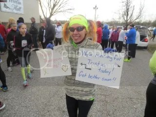 Me with the signs for Trinitie before running the Fast Freddie Five Mile Foot Feast