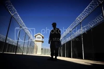 Nov. 15, 2009,  a U.S. captain silhouetted as he looks on cages of Bagram prison