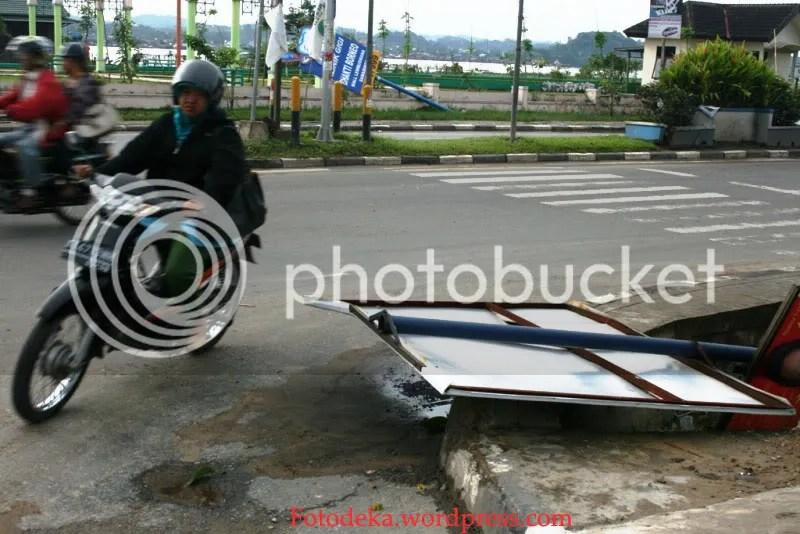 Pengguna jalan mesti berhati-hari karena baliho yang jatuh ini belum sempat disingkirkan agar tidak mengganggu.