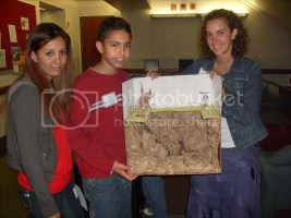 P.E. cofounder, Gabe, with JP team members Carla and Ray, holding up the Mammoth Site project.