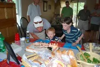 Troy getting help blowing out his birthday candles