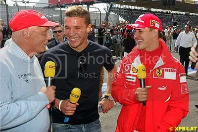 Niki Lauda and Michael Schumacher (with footballer Lukas Podolski centre)