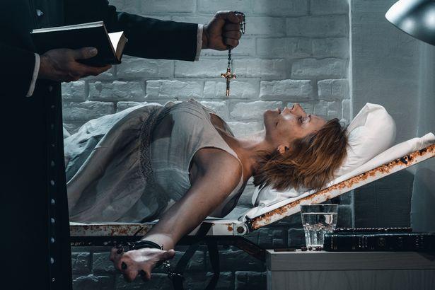 Vieux prêtre effectuant un rituel d'exorcisme traditionnel de jeune femme possédée dans une chambre d'hôpital sombre