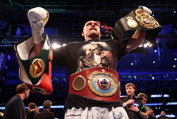 Oleksandr Usyk poses with his title belts