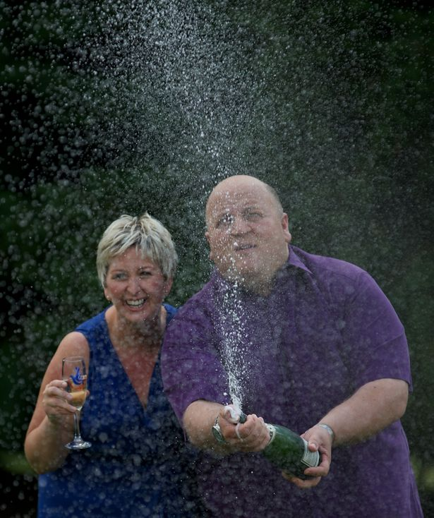 Adrian and Gillian Bayford spray champagne after winning more than £148 million on the EuroMillions