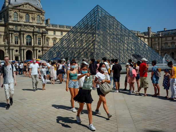 People walk past the Louvre in Paris on August 12, 2020. Temperatures in Paris are expected to reach 36 degrees Celsius (100.4 Fahrenheit) on Wednesday afternoon.