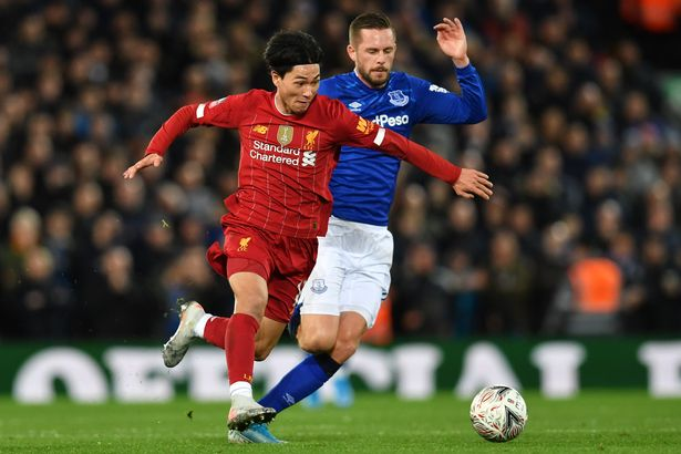 Takumi Minamino vies with Gylfi Sigurdsson during the FA Cup third round match between Liverpool and Everton at Anfield