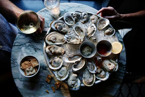 A couple enjoying raw oysters and champagne at a bar.