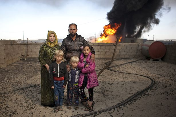 A family stand on the roof of their home in Qayyarah, with a burning oil well behind them