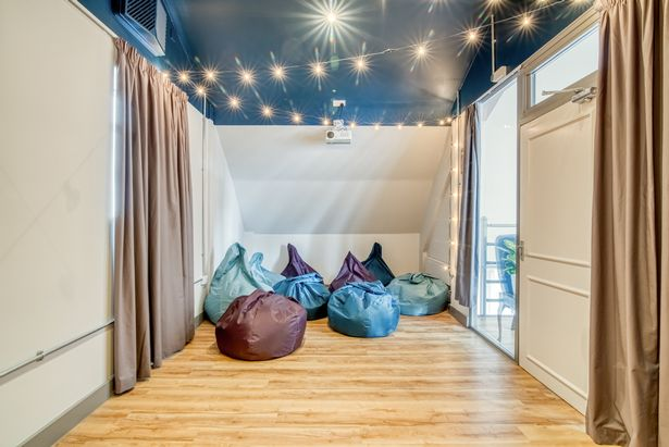 A private screening room at one of the Selina Hotels with bean bags and colourful lights