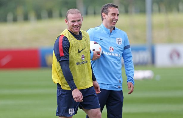 Wayne Rooney (L) jokes with coach Gary Neville