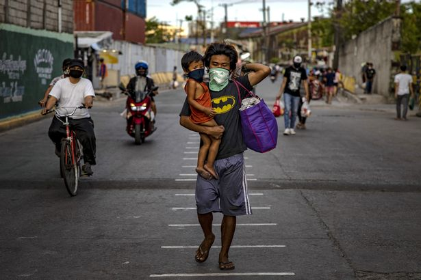 A man and his son wear facemasks in Manila, the country's capital