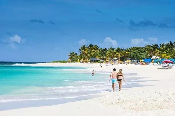 Ein paar Händchen haltend am Strand von Shoal Bay East auf der karibischen Insel Anguilla
