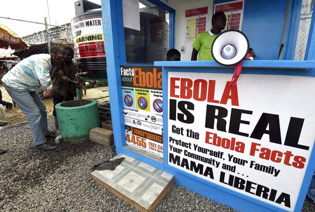 Liberians wash their hands next to an Ebola information and sanitation station
