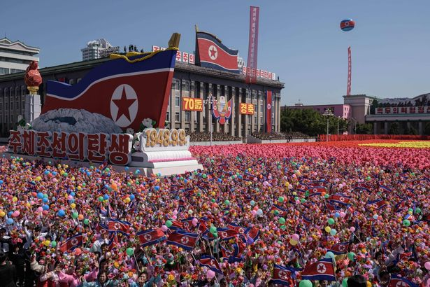 Participants wave flowers as they march past a balcony from where North Korea's leader Kim Jong Un was watching, during a mass rally on Kim Il Sung square in Pyongyang