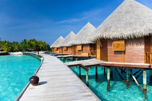 Eine Promenade führt zu Villen über dem Wasser mit Strohdächern auf den Malediven und dem türkisfarbenen Meerwasser