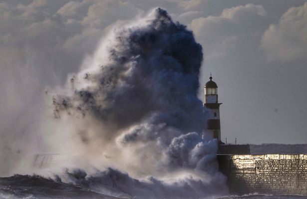 Waves crash over the walls next to Seaham Lighthouse