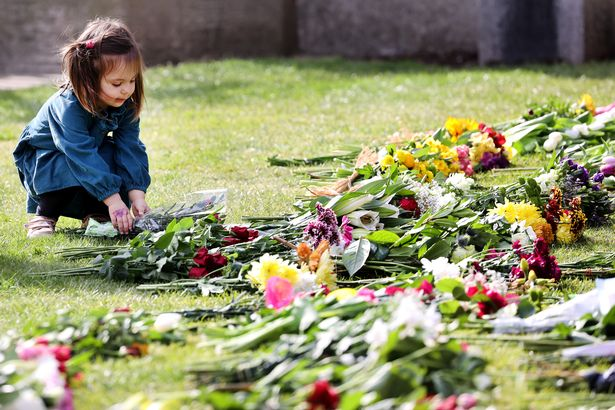 A child lays flowers outside of Windsor Castle after Prince Philip's death