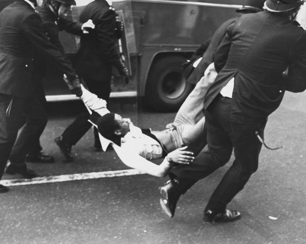 Police officers carrying an arrested man by the arms and legs after violence erupts in Brixton in April 1981