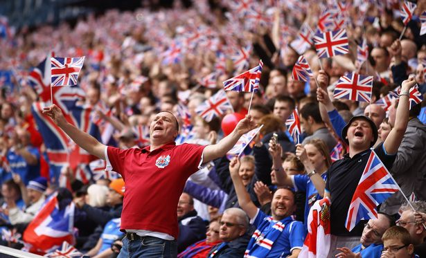Rangers supporters wave Union Jack flags during the Clydesdale Bank Premier League match between Rangers and Celtic at Ibrox Stadium salutes his supporters
