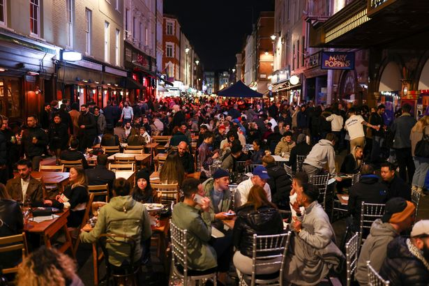 People dine and party along a street in Soho
