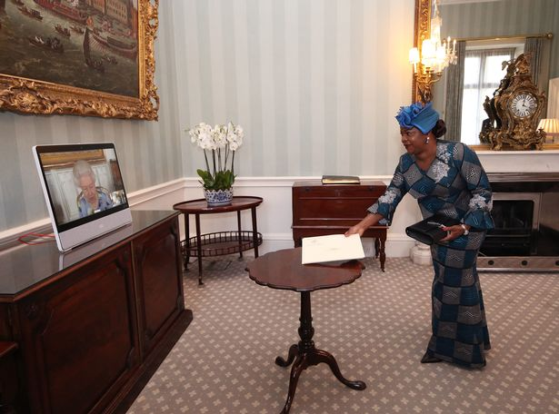Queen Elizabeth II appears on a screen by videolink from Windsor Castle, where she is in residence, during a virtual audience to receive Her Excellency Sara Affoue Amani, the Ambassador of Cote d'Ivoire, at Buckingham Palace, London