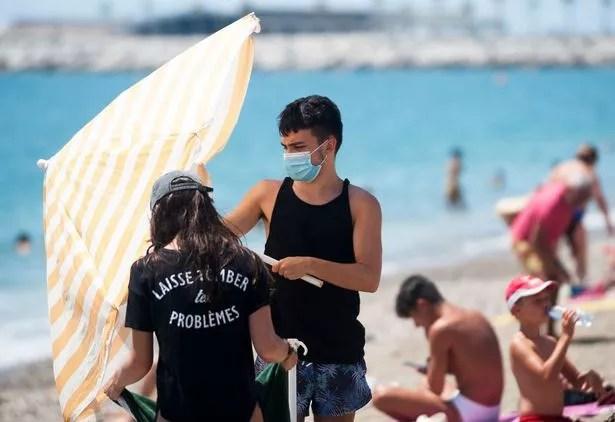 A man wearing a face mask is seen opening an umbrella at La Malagueta beach amid coronavirus crisis
