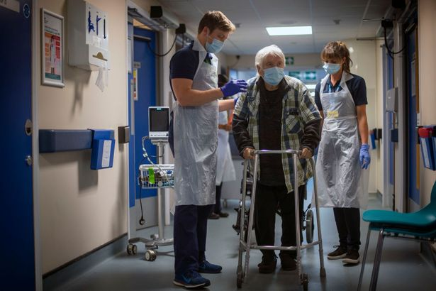 Rehab Support workers perform a physiotherapy treatment on patient Michael Kidd, 82, as the first patients are admitted to the NHS Seacole Centre at Headley Court, Surrey