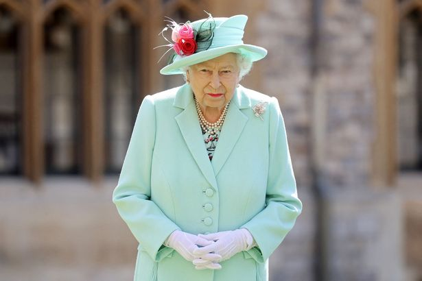 Queen Elizabeth II poses after confering the honour of a knighthood upon 100-year-old veteran Captain Tom Moore