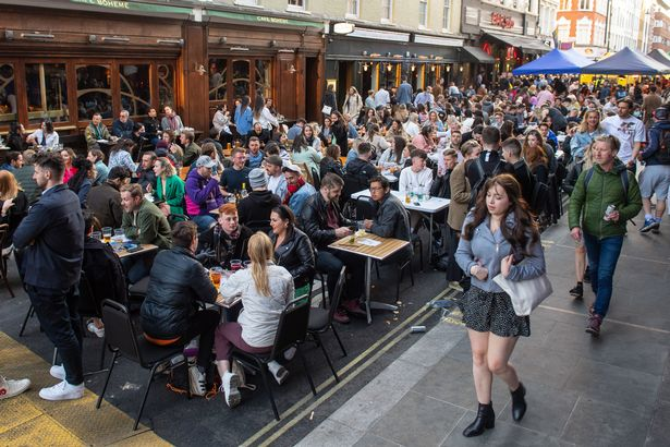 People eat and drink at outside tables on Saturday evening in Soho, central London