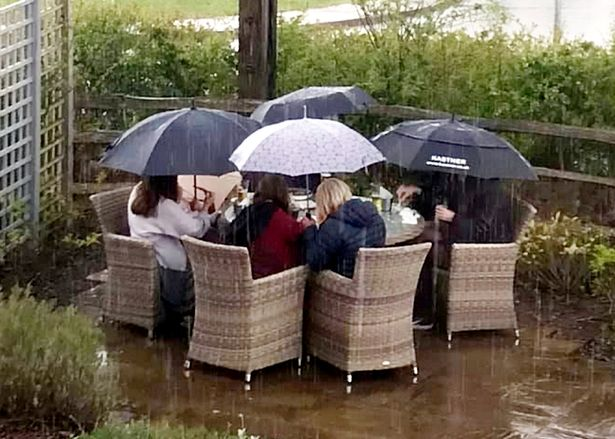 A group of hardy pub goers have raised a smile after being pictured enjoying an outdoor pint - in the pouring rain