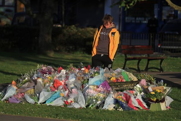 Patrick James, the son of PCSO Julia James, looks at floral tributes left near her family home