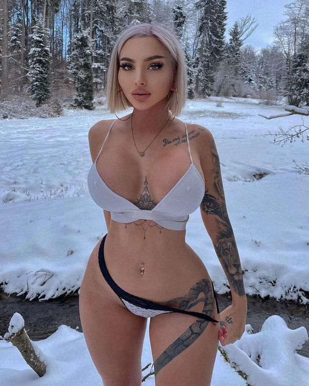 A tanned woman standing in the snow. She is wearing lingerie and has tattoos on her arm and legs