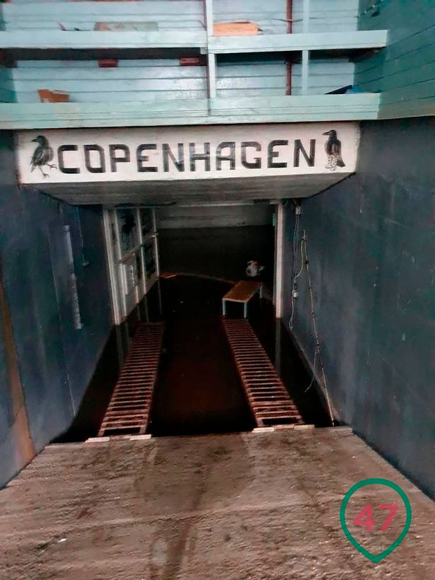 The entrance has a sign that reads 'Copenhagen' and has symbols associated with the Italian mafia