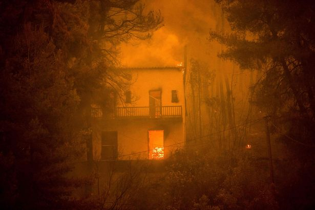 A house is burning as forest fires approach
