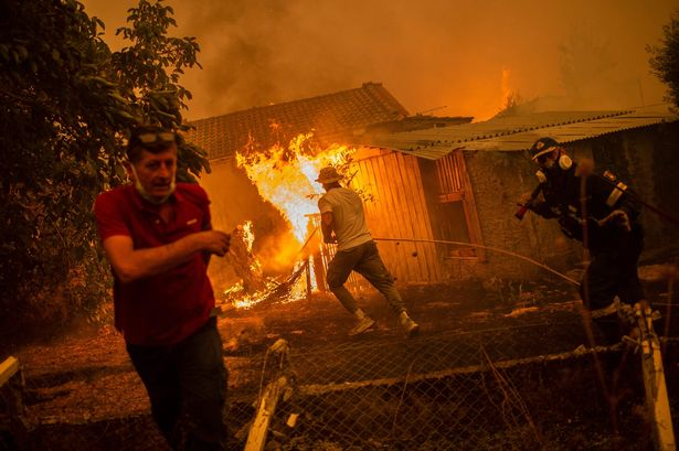 A firefighter and locals rush to a burning house