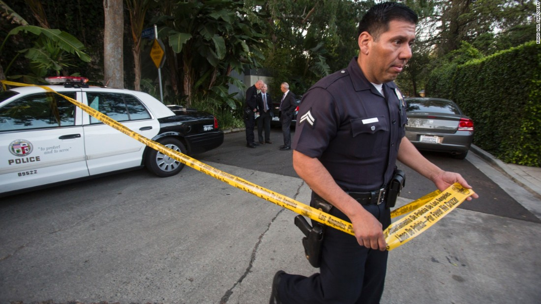 A police officer creates a perimeter outside a home in the Hollywood Hills area of Los Angeles, Tuesday, March 31, 2015. Police say a man was found dead at the home of Andrew Getty, heir to Getty oil fortune. (AP Photo/Ringo H.W. Chiu)