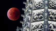 The eclipsed supermoon is seen next to one of the steeples of the Cologne Cathedral in Germany.