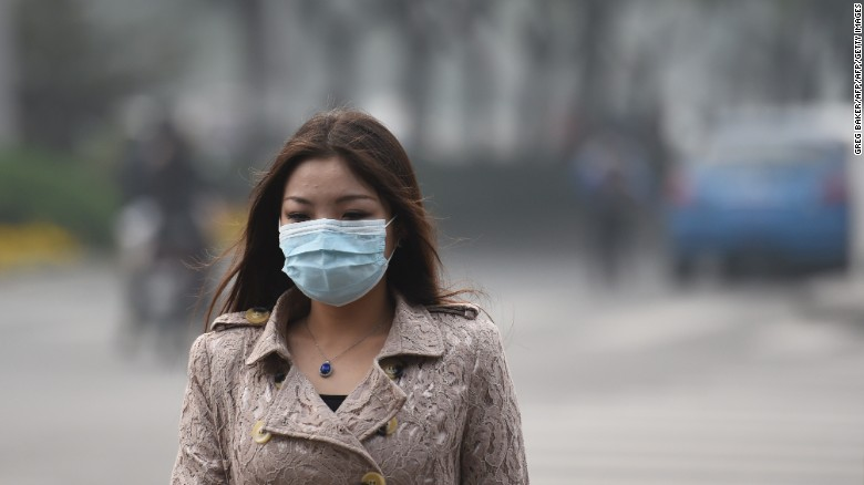 A woman wearing a mask on a heavily polluted day in Beijing.