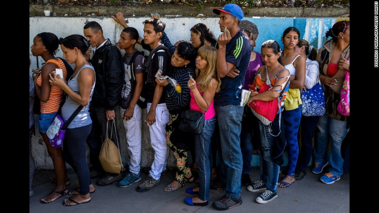 People line up to buy basic food and household items outside a supermarket in Caracas, on September 28, 2016.
