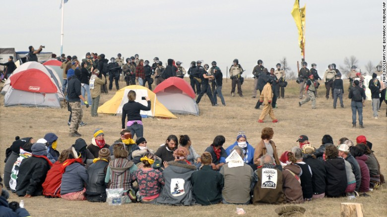 Dakota Access Pipeline protesters sit in a prayer circle at the Front Line Camp as a line of law enforcement officers make their way across the camp to remove the protesters and relocate to the overflow camp a few miles to the south on Highway 1806 in Morton County, North Dakota, on Thursday, October 27.