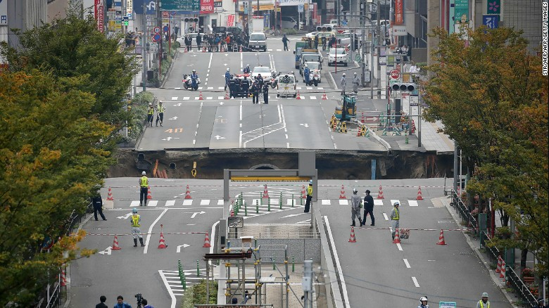 This photo shows a giant sinkhole (C) in a five-lane urban boulevard, eroding soil and exposing underground steel columns supporting commercial buildings in Fukuoka, southwestern Japan, on November 8, 2016. No injuries were reported as the accident occurred in the early morning hours.      / AFP / JIJI PRESS / STR / Japan OUT        (Photo credit should read STR/AFP/Getty Images)