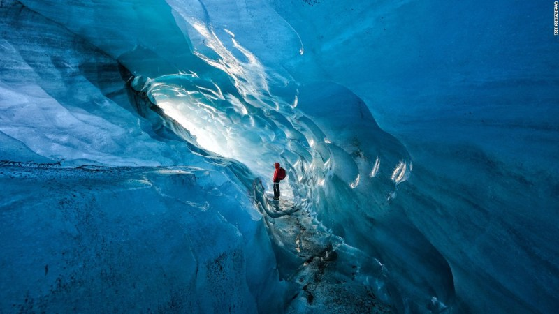 "Photo: Tom Schifanella, USA: ""Since 2000, Icelandic glaciers have lost 12% of their size, in less than 15 years. Pictured here, Icelandic guide Hanna Pétursdóttir admires an ice cave inside the Svínafellsjökull Glacier, which she notes is rapidly expanding due to the effects of global warming,"" wrote Schifanella."