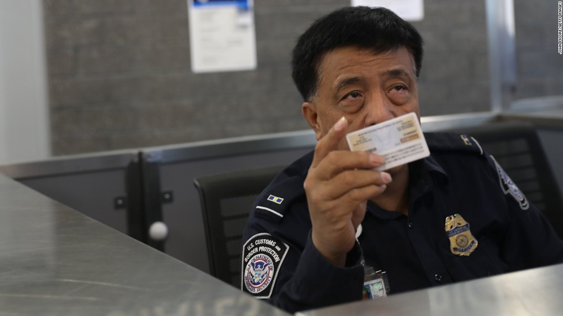 A Customs and Border Protection officer checks IDs as people enter the US from Mexico in San Ysidro, California.