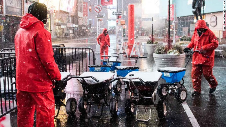 Ahygia McDowell, left, and Ronnie Wade, workers with the Times Square Alliance, prepare to salt the sidewalks in Times Square during the early hours of a winter storm in New York, U.S., February 9, 2017. Mark Kauzlarich for CNN