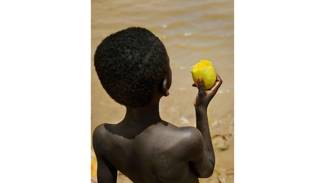 Boy with mango at Lake Bam, near the town of Kongoussi, Burkina Faso